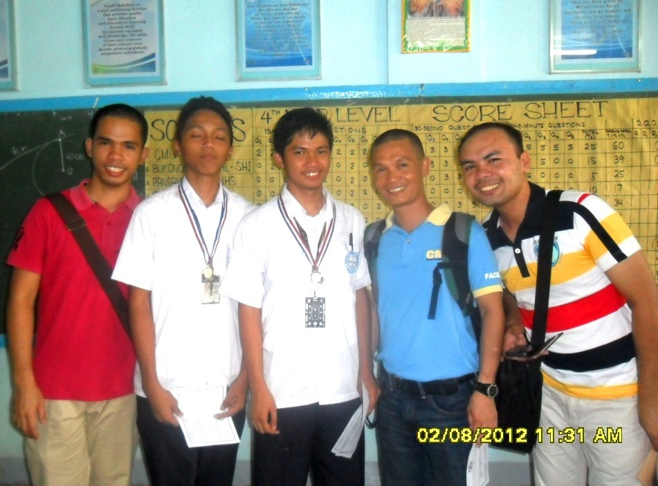 The champions John Glenn L. Lambayon and Elwin Jay J. Tano (2nd and 3rd from left) with Coach  Prof. Joemar B. Capuyan  (extreme right)  and two other faculty members in red and blue shirt.